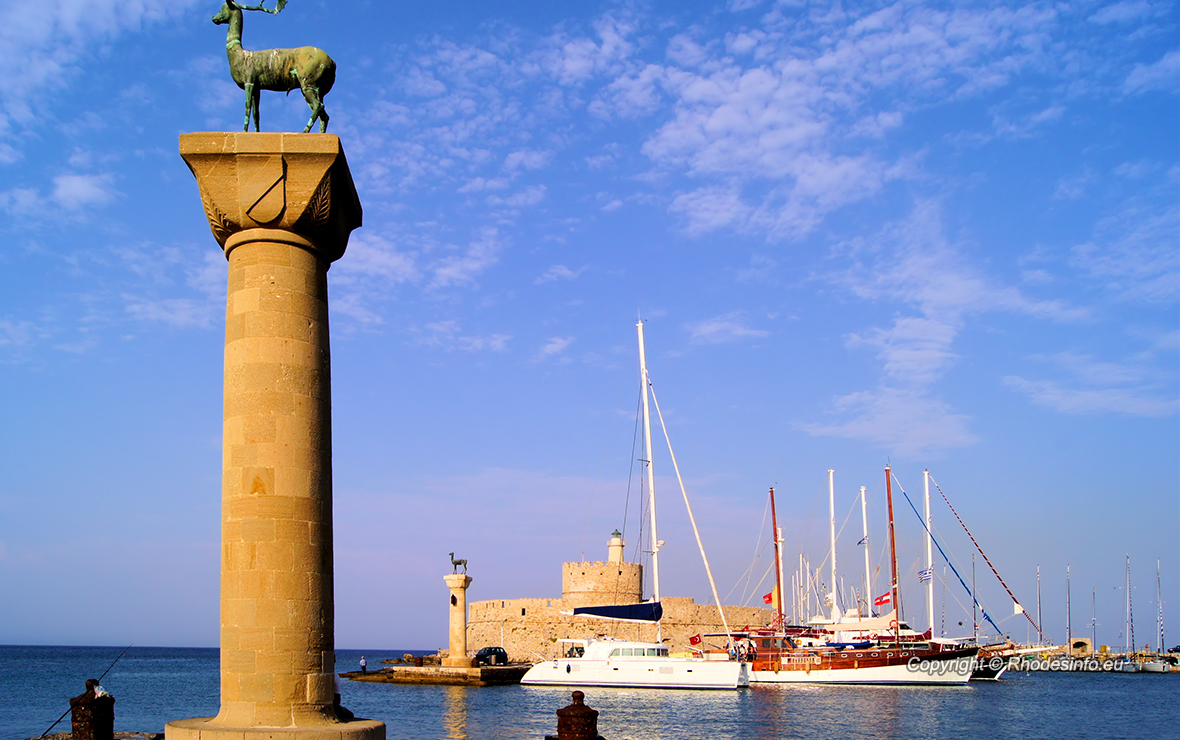 Rhodes Mandraki harbor with castle and symbolic deer statues, Greece